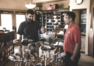 a man who choose a golf club to buy it