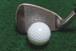 a golf iron with a golf ball