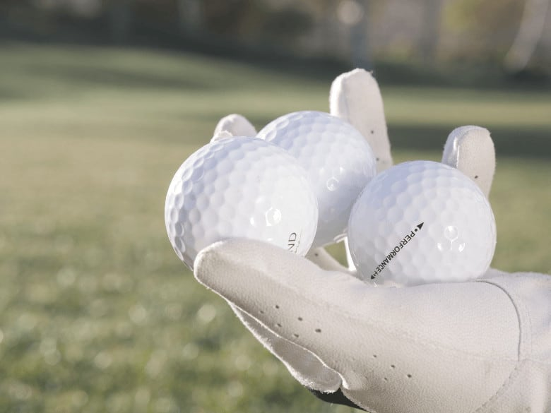 a golfer is taking some golf balls to choose the best one for him