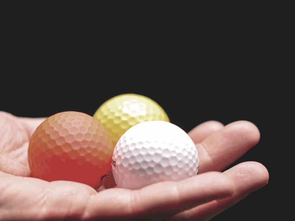 a gollfer hold three golf balls on his hand to choose one of them